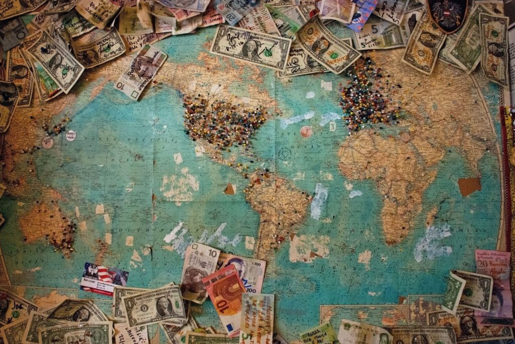 old world map with pins where people have visited with local currencies